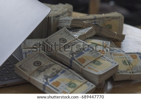 Stack of money on laptop