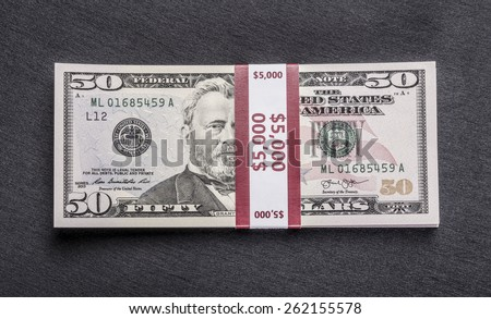 Stack of money wrapped in currency strap - $ 50 fifty-dollar bills on black background. Top view - stock photo