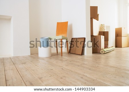 Stack of moving boxes and chair in new house - stock photo