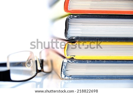 Stack of multicolored books with black nerd glasses