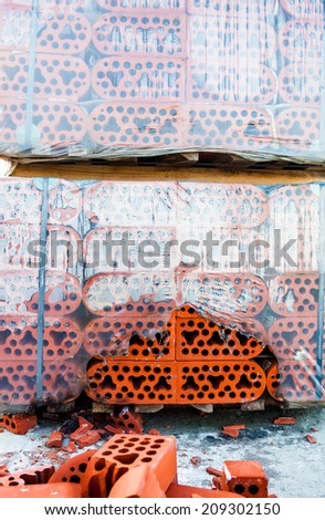 Stack of new silicate bricks in misted polyethylene with the pile of beaten bricks nearby. - stock photo