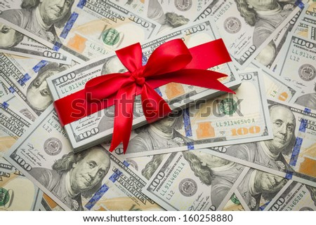 Stack of Newly Designed U.S. One Hundred Dollar Bills Gift Wrapped in Red Bow. - stock photo