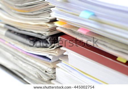 Stack of newspaper and documents with high key tone and blur focus,newspaper and documents on desk at business office.