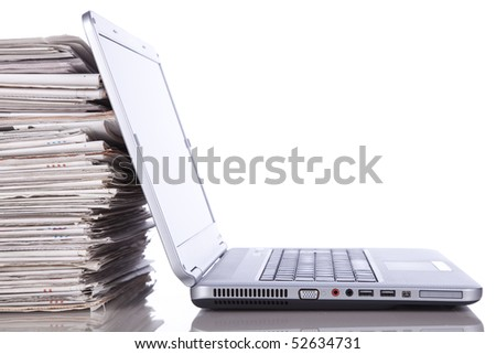 stack of newspaper next to a laptop (isolated on white) - stock photo
