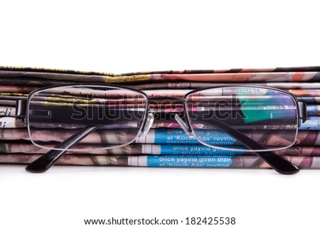 Stack of newspapers and eye glasses, isolated on white background.