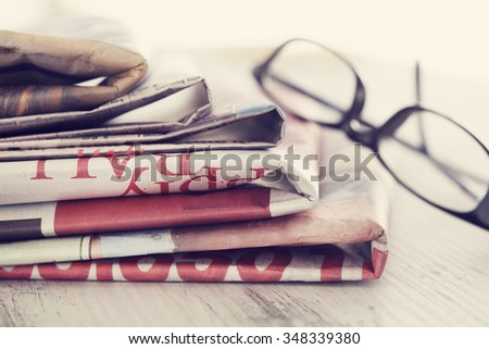 Stack of newspapers and eyeglasses - stock photo
