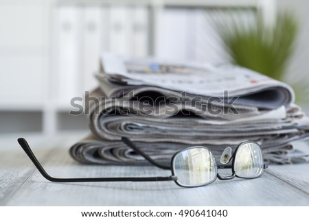 Stack of newspapers and eyeglasses