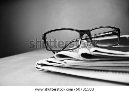 Stack of newspapers and glasses in black and white - stock photo