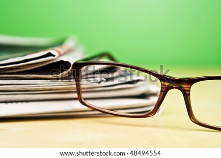 Stack of newspapers and glasses lying on table on green background