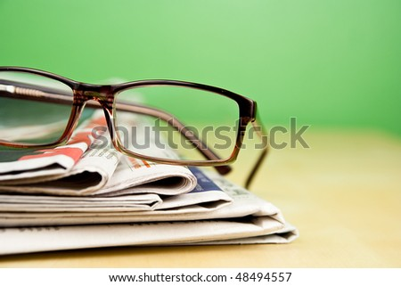 Stack of newspapers and glasses lying on table on green background - stock photo
