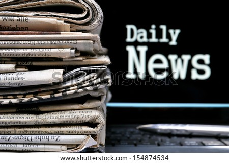 Stack of newspapers beside the lettering Daily News - stock photo