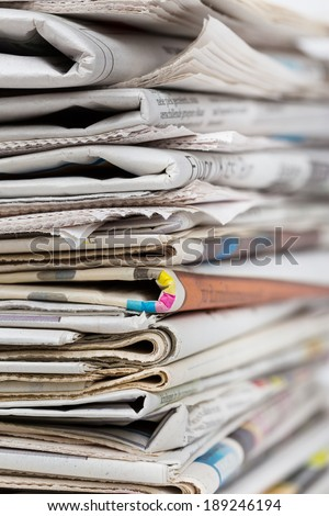 Stack of newspapers closeup shot. News and updates, journalism, power of the media, newspaper and magazine ads and subscription concept. Great as a web page banner, article illustration and more. - stock photo