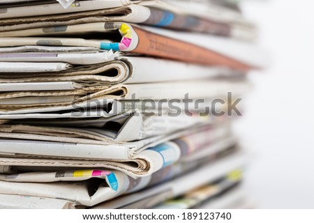 Stack of newspapers, closeup shot with focus on foreground and blur. Morning news, journalism, power of the media, newspaper and magazine subscription and ads concept.  - stock photo