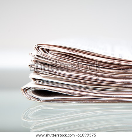 stack of newspapers on glass table