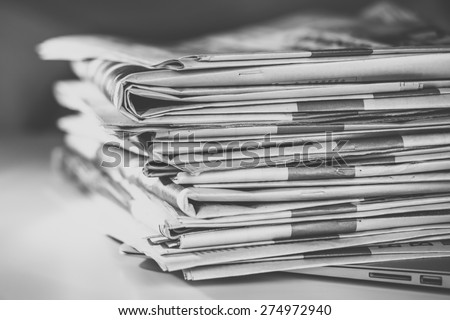 Stack of newspapers, placed on a laptop, edited in black and white