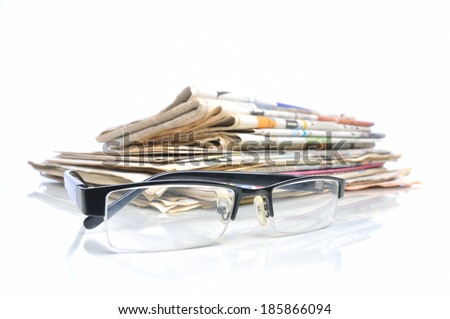 Stack of newspapers with glasses in front - stock photo