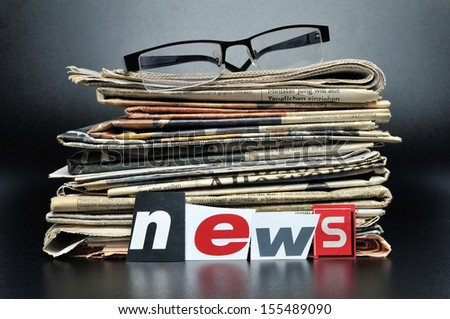 Stack of newspapers with glasses on top - stock photo