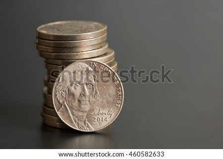 Stack of Nickels on a Gray Background