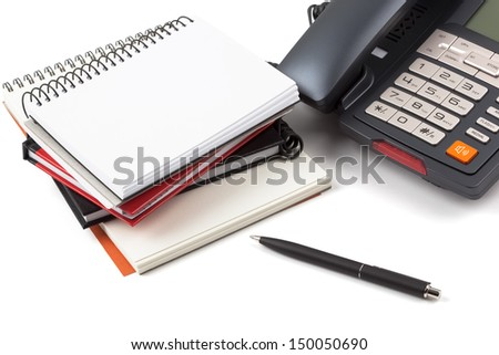 Stack of notebooks, a ballpoint pen and a digital phone on white background. - stock photo