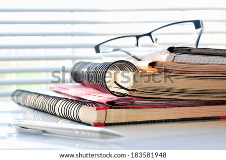 Stack of office folders with glasses and ballpoint in front of a window - stock photo