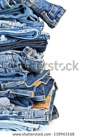 Stack of old and worn blue jeans over a white background - stock photo