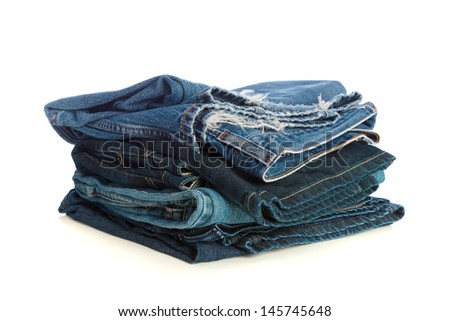 Stack of old blue jeans on a white background
