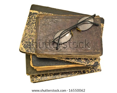 stack of old books and glasses on it against white background