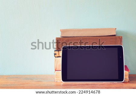 stack of old books and tablet over wooden shelf. new technology concept. room for text - stock photo