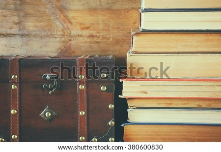 stack of old books next to antique wooden chest on wooden shelf. vintage filtered and toned - stock photo