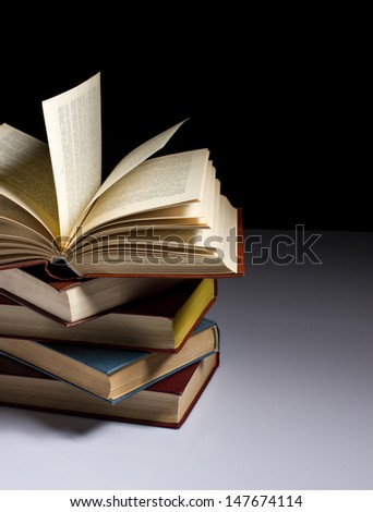 stack of old books on the table, on dark background - stock photo