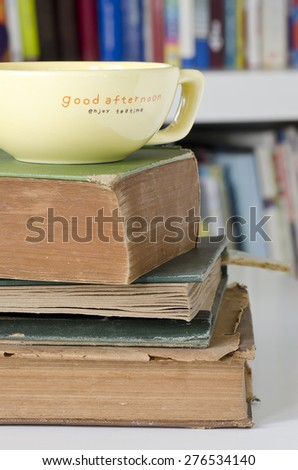 Stack of old books on the table with yellow cup on top. - stock photo