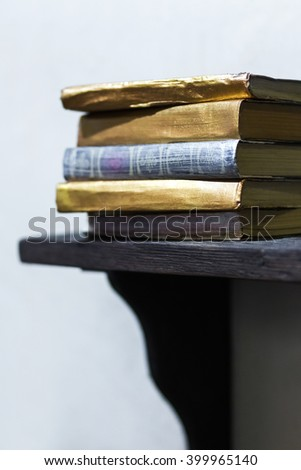 Stack of old books with golden covers on the shelf - stock photo