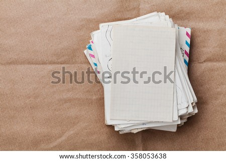 Stack of old envelopes and letters on kraft paper, top view - stock photo