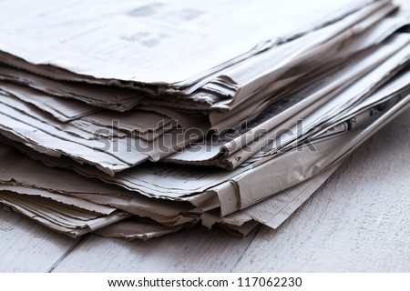 Stack of old newspapers on wooden table - stock photo