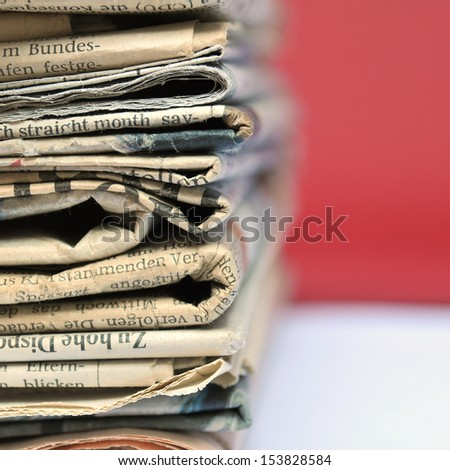 Stack of old newspapers with red background - stock photo