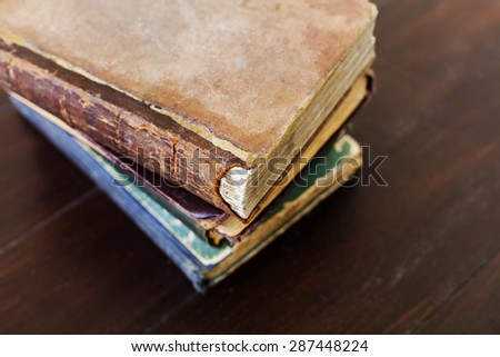Stack of old vintage books on dark wooden background, selective focus and shallow dof - stock photo