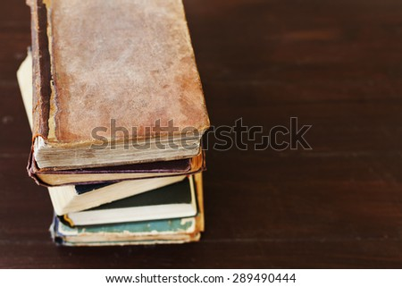 Stack of old vintage books on wooden background, theme of the reading and education, selective focus and shallow dof - stock photo