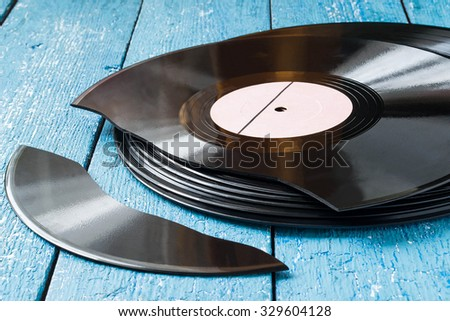 Stack of old vinyl records on a blue wooden background, one record broken - stock photo