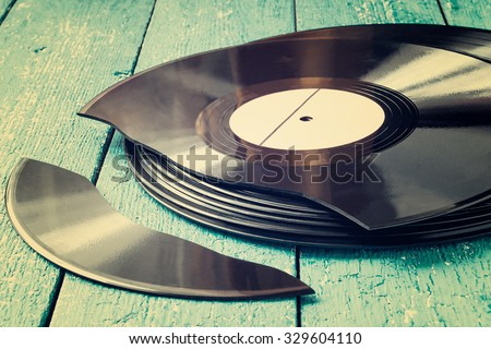 Stack of old vinyl records on a blue wooden background, one record broken. Toned photo - stock photo