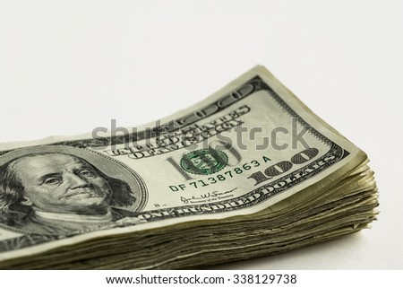 Stack of one hundred dollar bills on white background. Shallow depth of field with the focus on Franklin's right eye and corner one hundred.
