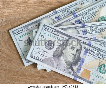 Stack of one hundred dollar bills  on wood table - stock photo