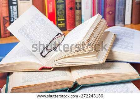 Stack of open books and glasses on the desk in the library - stock photo