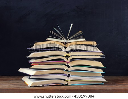 Stack of open books on the table in the background of a school blackboard. Back to school. - stock photo