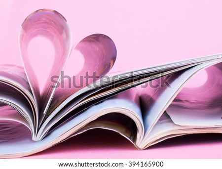 Stack of open magazines on a pink background. The heart of the pages of the magazine. Information - stock photo