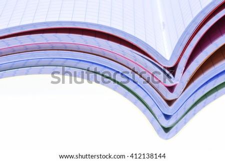 Stack of opened exercise books isolated on white background - stock photo