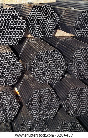 stack of packed rounded welded steel pipes - stock photo