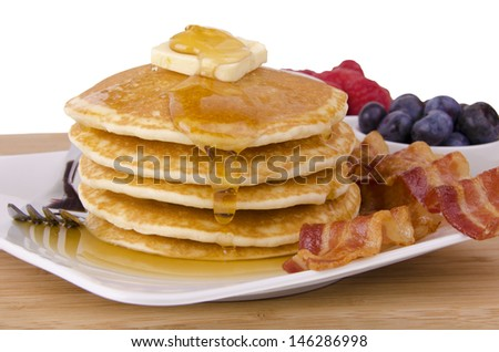 Stack of pancakes and bacon with fruits on background. Front view.