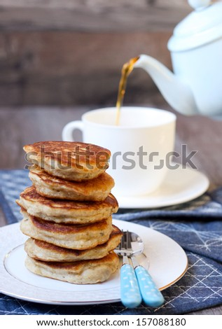 Stack of pancakes and pouring tea into the cup - stock photo