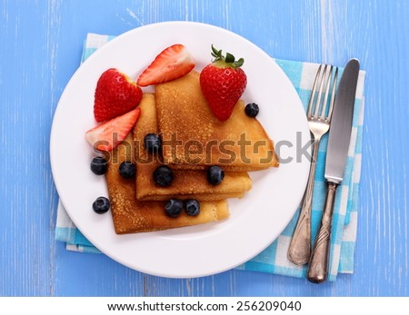 Stack of pancakes, fresh strawberry blueberry, cutlery, top view - stock photo