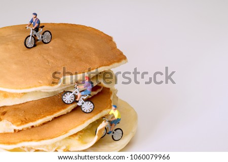 Stack of pancakes isolated on white background with miniature figures of mountain bikers climbing over it. Concept image for sport, travel, exploring, eating, breakfast, fastfood or restaurant.